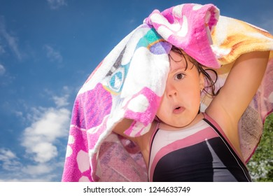 Girl drying herself with a colorful towel after swimming in a pool in summer