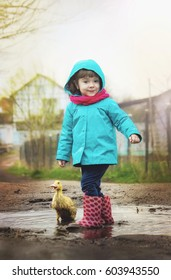 Girl with a duck on his arm. Selective focus.