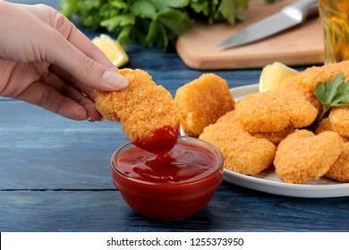 Girl dunks chicken nuggets in ketchup close-up on blue wooden background. fast food