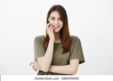 Girl eager share interesting rumor with friend, trying keep intrigue. Portrait of interested good-looking woman in green t-shirt, biting finger and smiling curiously, having idea or desire