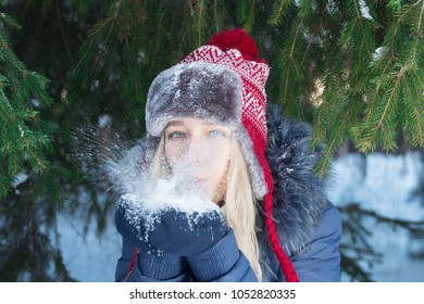 Girl in ear-flap hat blows out snow near green fir tree outdoor in winter day