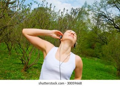 girl in ear-phones in park