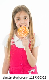 Girl eat lollipop isolated on white. Little child enjoy candy on stick. Happy kid smile with swirl caramel. Candyshop concept. Childhood and happiness. Sweet mood. My favourite meal.
