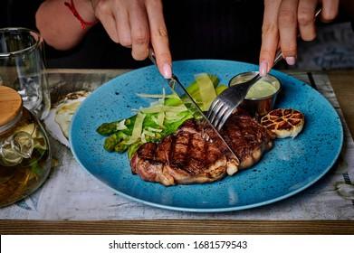 girl eating beef steak and drinking tea