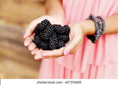 Girl eating berries on wooden background. Blackberry in hand