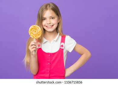 Girl eating big candy on stick or lollipop. Sweet childhood concept. Kid with long hair likes sweets and treats. Girl on smiling face holds giant colorful lollipop in hand, violet background.