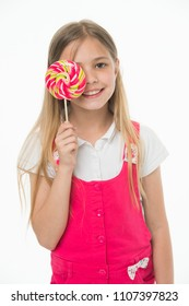 Girl eating big candy on stick or lollipop. Girl on smiling face holds giant colorful lollipop in hand, isolated on white background. Kid with long hair likes sweets and treats. Sweet tooth concept.