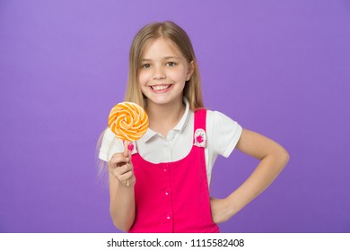 Girl eating big candy on stick or lollipop. Sweet childhood concept. Girl on smiling face holds giant colorful lollipop in hand, violet background. Kid with long hair likes sweets and treats.
