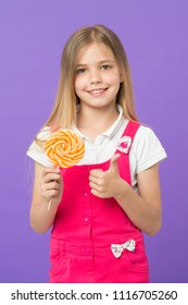 Girl eating big lollipop and shows thumb up. Sweet childhood concept. Kid with long hair likes sweets and treats. Girl on smiling face holds giant colorful lollipop in hand, violet background.
