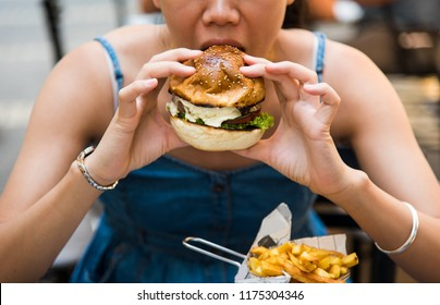 Girl eating burger in the restaurant close up