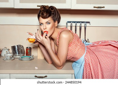 Girl eating cake and licking her fingers, she was lying on the table.