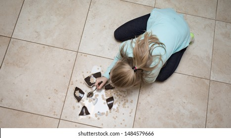 A girl eating cereal from a shattered bowl on the kitchen floor.