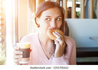 A girl is eating a cheeseburger in a cafe