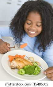 Girl eating chicken and vegetable dinner at home