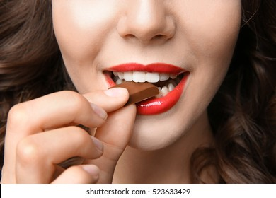 Girl eating chocolate, closeup