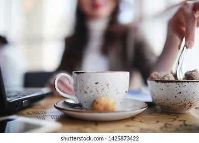Girl eating coffee cakes and drinking coffee