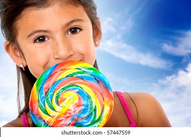 Girl eating a colorful candy with the sky on the background