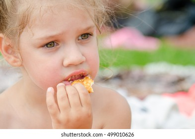 Girl eating cookies and drinking juice from a plastic disposable cup