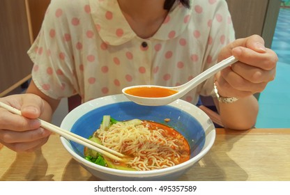 The girl eating noodle with soup in the spoon