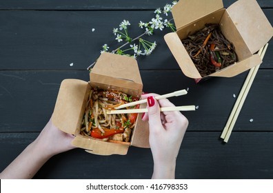 Girl eating noodles out of the box