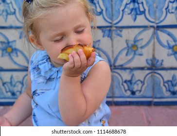 The girl is eating Pasteis de Belem egg tart, typical Portuguese dessert