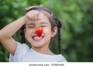 Girl eating strawberries in the berry meadow