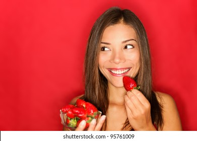 Girl eating strawberries smiling happy looking to the side on red background with copy space. Beautiful young mixed race Asian and Caucasian woman eating healthy.
