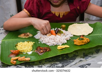 Girl eating traditional Onam sadhya using right hand, boiled rice, served with curries Parippu, Sambar, Pulisseri, Kaalan, Avial, Olan, Pachadi, Naranga , Papadum, Payasam, Banana, Buttermilk, chips.