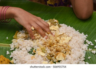 Girl eating traditional Onam sadhya using right hand, boiled red Kerala rice, served with curries Parippu, Sambar, Pulisseri, Kaalan, Avial, Olan, Pachadi, Papadum, Payasam in banana green leaf