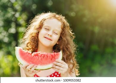 Girl eating watermelon enjoying closing her eyes. Diet, vitamins, healthy food concept.