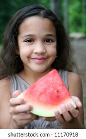 Girl eating watermelon in her yard