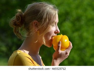 girl eating yellow pepper