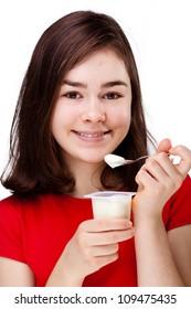 Girl eating yogurt isolated on white background