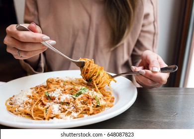 girl eats Italian pasta with tomato, meat. Close-up spaghetti Bolognese wind it around a fork with a spoon. Parmesan cheese