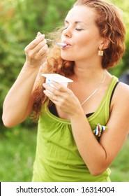 girl eats yogurt and has closed eye from pleasure