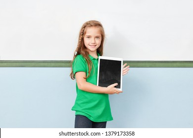 Girl as elementary school student learns with a tablet computer