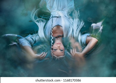 A girl elf in a white dress is floating in the water. Model in a medieval dress with pigtails floating in the lake