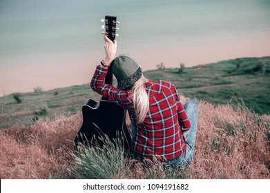 girl in an embrace with a guitar is sad on a cliff near the ocean