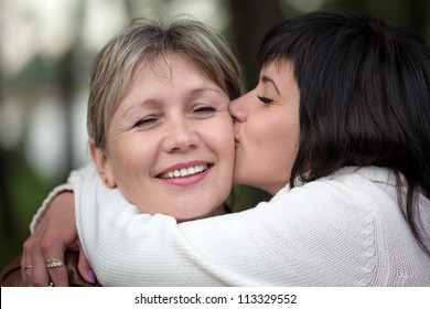 The girl embraces and kisses the woman