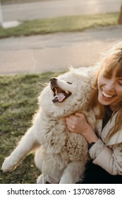 girl embraces  white samoyed dog at sunset and smiles