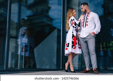The girl in an embroidered dress embraces the guy and looks at him. The guy in an embroidered shirt holds his hands in his pockets. building with glass walls