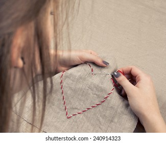 Girl embroidering a heart shape on beige linen fabric; top view