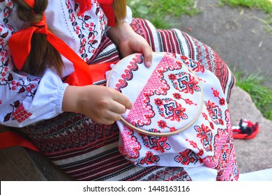 Girl Embroidery Rushnik.Hands of girl woman female in ukrainian traditional shirt sewing embroidery pattern in embroidery frame. Close up. Selective focus
