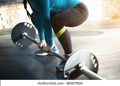 The girl is engaged in bodybuilding. Deadlift by women in black and blue clothing.