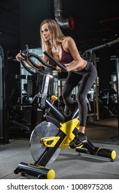 The girl is engaged in an exercise bike, personal training in the gym.