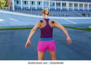 The girl is engaged in fitness with an electrostimulator. Exercises and load on the back muscles with an electrostimulator.