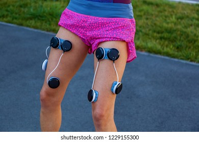 The girl is engaged in fitness with an electrostimulator. Exercises and load on the leg muscles with an electrostimulator.