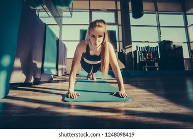 The girl is engaged in fitness in the gym. Toned image. concept of a healthy lifestyle and exercise in the gym. The girl doing female push-ups and plank during training close up