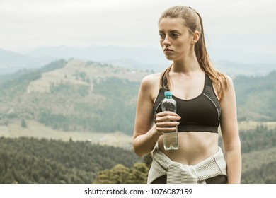 The girl is engaged in fitness in the mountain forest. Rest and drinking water from the bottle after the training.
