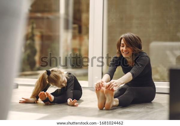 Mädchen ist in der Turntechnik beschäftigt. Familie in einem Yogastudio. Kind in einer schwarzen Sportkleidung.